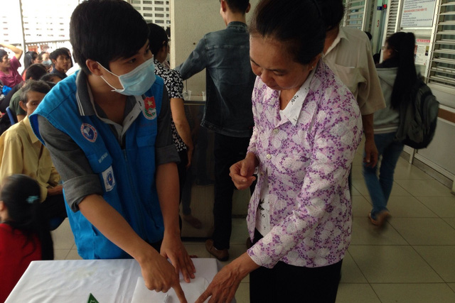 Tình nguyện viên của Trung tâm Công tác xã hội Thanh niên TP HCM tận tình hướng dẫn bệnh nhân các thủ tục khám bệnh tại Bệnh viện Chợ Rẫy.   ảnh: T. Giang