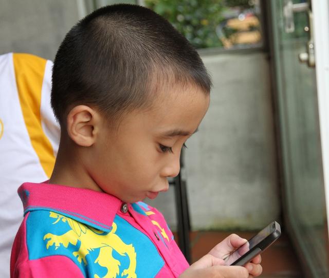 Các bậc cha mẹ cần kiểm soát chặt chẽ khi cho trẻ sử dụng các thiết bị di động thông minh. Ảnh: Chí Cường