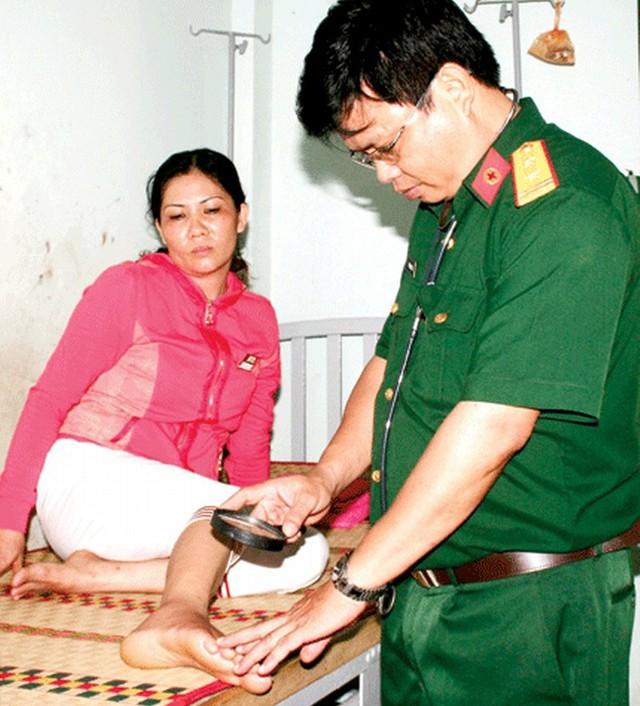 Trung tá-bác sĩ Vũ Ngọc Lương đang thăm khám một nạn nhân bị rắn độc cắn tại Trại Rắn Đồng Tâm.