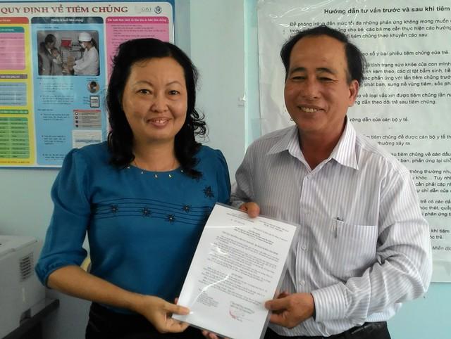Đại diện Chi cục dân số, ông Trần Văn Trị, trao quyết định bàn giao máy siêu âm đến lãnh đạo Trung tâm Y tế dự phòng Q.2.
