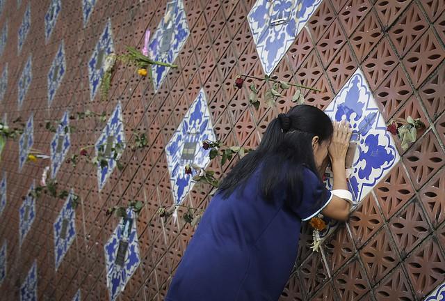 Một người phụ nữ đang cầu nguyện trên một bức tường tưởng niệm hiển thị tên của các nạn nhân trong đợt sóng thần ngày 26/12/ 2014 tại Ban Nam Khem, Thái Lan.