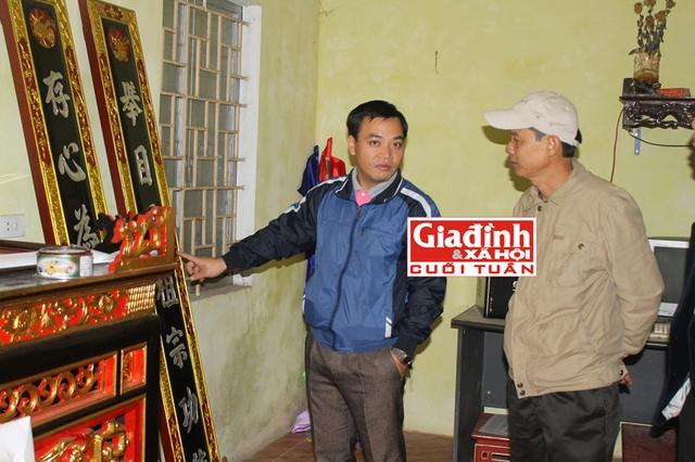 Ông Chung (bên phải) đang giới thiệu với du khách về những sản phẩm dát vàng trên hoành phi, câu đối.