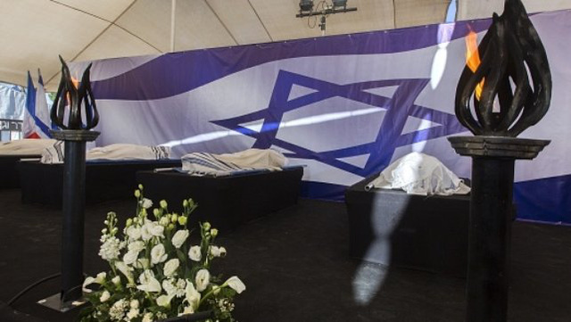 The bodies of four victims are placed in front of an Israeli national flag at a cemetery in Jerusalem