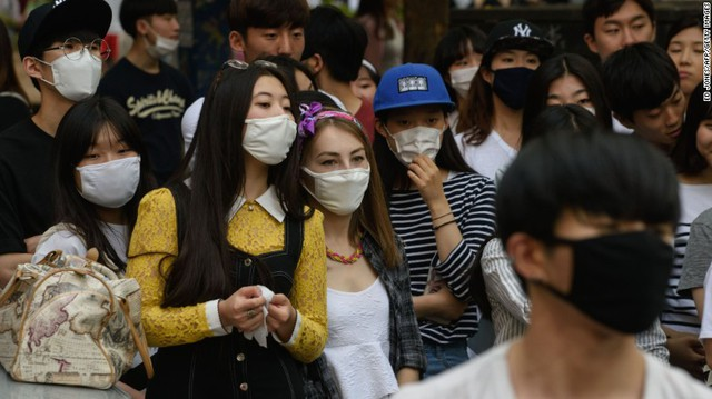 People wearing face masks watch a K-Pop performance on a street in the popular student area of Hongdae in Seoul on June 7, 2015. South Korea has grappled with an outbreak that was threatening to spread nationwide.