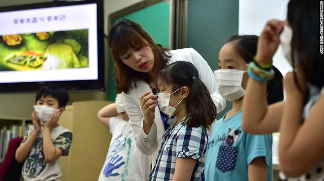 South Korean students put on face masks during a special class on the MERS virus at an elementary school in Seoul on June 3.