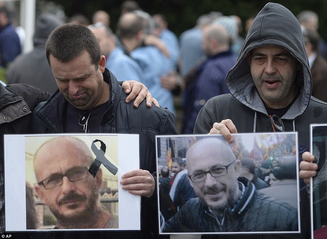 Workers from the Delphi factory in Spain hold a picture of their colleague, Manuel Rives, who died in the crash on Tuesday morning