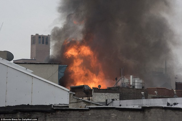 Raging: A rooftop view of the massive fire rising above Second Avenue earlier in the day Thursday