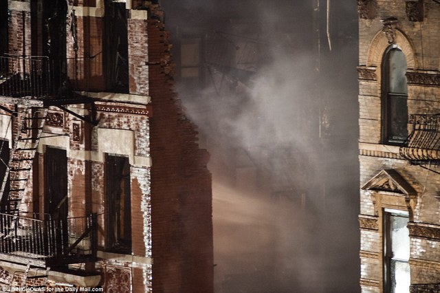 Gaping hole: Smoke billows from a gap between two buildings where an old tenement house had once stood