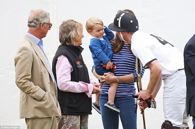 After such a busy day, its no wonder that George looks less than interested after his fathers game is over. William talks to his sceptical-looking son while Prince Charles looks on