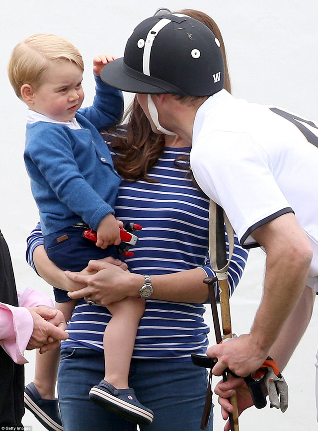 Well played! Prince George tentatively touches his father Prince Williams helmet before pulling his hand away