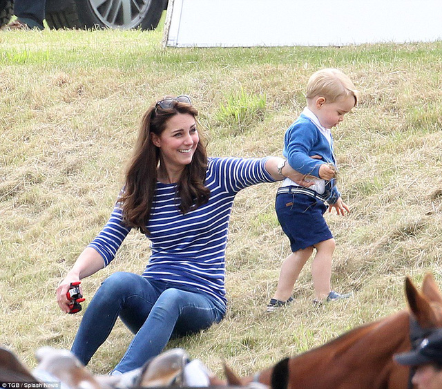 An amused Kate holds Georges toy car for him as he goes for an adventurous wander up the hill