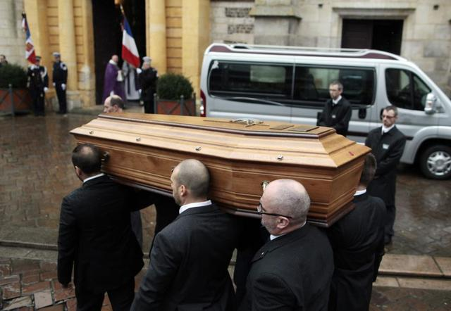 Relatives of Franck Brinsolaro, the police officer charged with protecting late Charlie Hebdo editor Stephane Charbonnier, carry the cops coffin into Sainte Croix Church on Thursday.