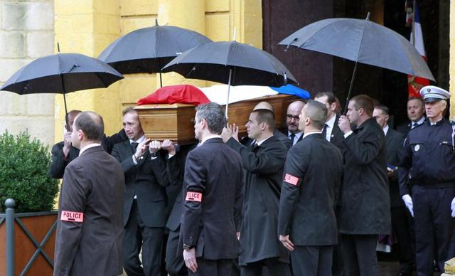 The coffin of police officer Franck Brinsolaro is carried out of Sainte Croix Church following the funeral ceremony Thursday.