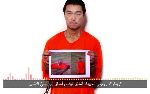 Con tin Kenji Goto cầm bức ảnh phiến quân hành quyết con tin Haruna Yukawa trong đoạn ghi âm. Ảnh: AFP