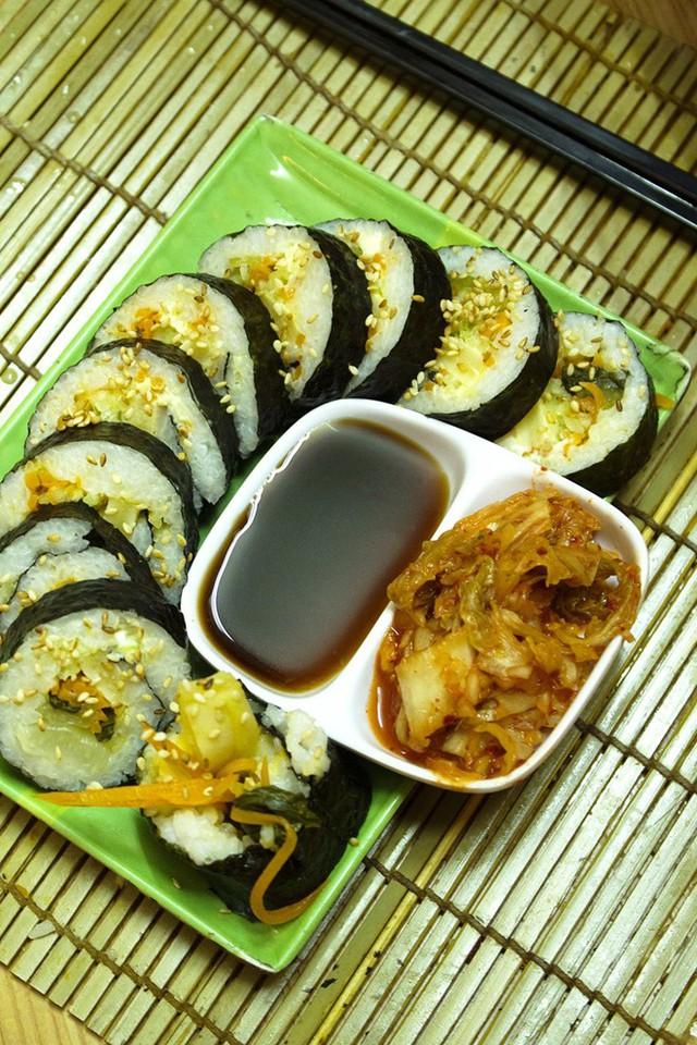 Dọn kimbap ra đĩa, rắc ít dầu mè lên trên, dọn ăn kèm kim chi và nước tương. Món ăn do quán Kim bắp (hẻm 337 Lê Văn Sỹ, quận Tân Bình, TP HCM) hướng dẫn.
