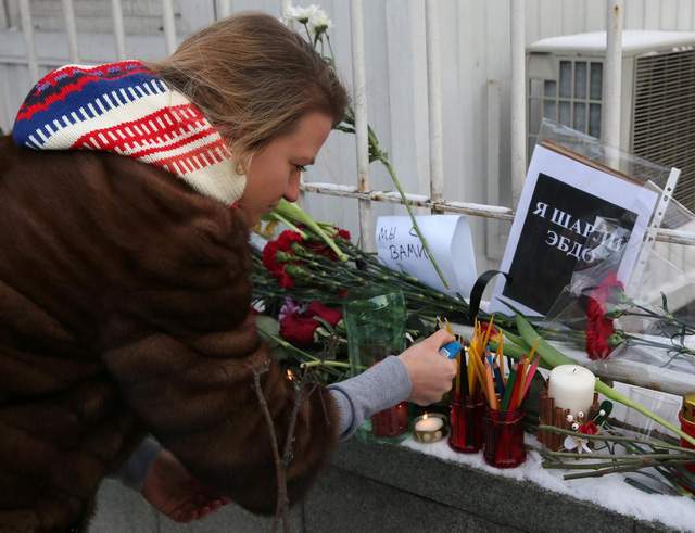 A Russian woman lights candles in front of the French embassy in Moscow, Russia, in solidarity with those killed or injured in yesterdays terror attack at the satirical magazine Charlie Hebdo.
