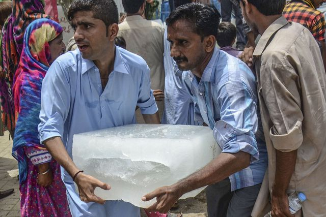 Pakistani men carry an ice block outside a hospital