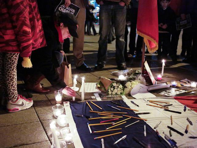 People place pens, pencils and candles around a French flag at a vigil outside the French consulate in Seattle, Washington, Wednesday night for the victims of the shooting at the Paris offices of the publication Charlie Hebdo.