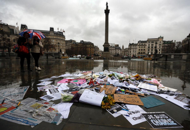 Flowers, pens and placards have been left at a memorial in Trafalgar Square, London, early Thursday morning to show solidarity with those killed in an attack at the Paris offices of weekly newspaper Charlie Hebdo.