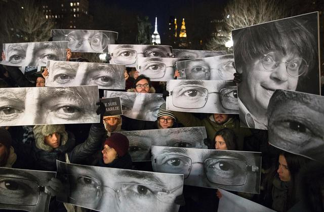 Mourners hold signs picturing the eyes of some of the victims of the terror attack on Charlie Hebdo magazine in Paris during a vigil Wednesday night in Manhattans Union Square.