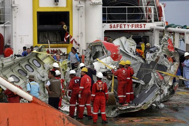 Đội cứu hộ trục vớt mảnh vỡ máy bay AirAsia từ biển Java và đưa lên bờ. Ảnh: AP