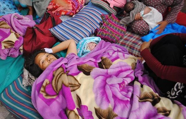 Cô Asha Shrestha nằm bên con gái mới sinh sau vụ động đất. Ảnh:
