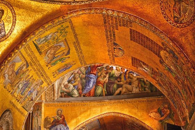 """Đặc điểm nổi bật nhất của nhà thờ là các tấm tranh trảm trên nền dát vàng bao phủ toàn bộ phía trong nhà thờ, khiến vương cung thánh đường St. Mark còn được mệnh danh là """"Nhà thờ vàng"""". Trước cửa sổ tầng trên còn có 4 tượng ngựa bằng đồng mạ vàng, mỗi tượng nặng tới 875 kg."""