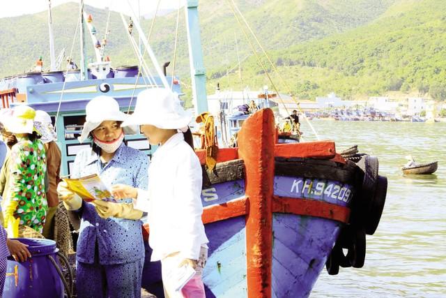 Cán bộ dân số huyện Cam Lâm - Khánh Hòa phát tài liệu truyền thông chăm sóc SKSS cho ngư dân tại các tàu cá. Ảnh: Dương Ngọc