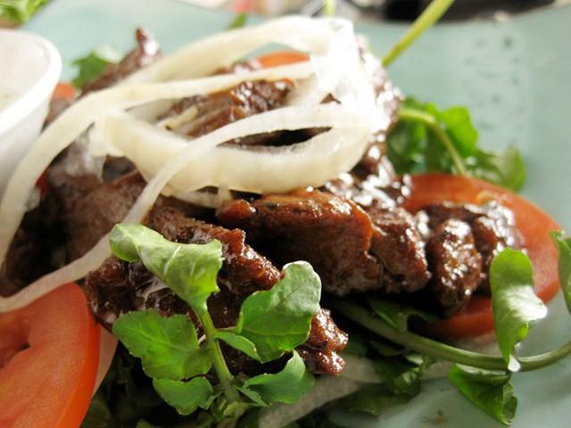 """15. Bò lúc lắc: Đây là món ăn có khởi nguồn từ ẩm thực Pháp, xuất hiện từ những năm 1960. Tên của món ăn này bắt nguồn từ hình dạng của miếng thịt bò: """"lúc lắc"""" nghĩa là miếng thịt bò to bằng cỡ một viên xúc xắc để có thể ăn bằng đũa dễ dàng hơn. Bò lúc lắc thường được ăn kèm với rau sống, hành tươi. Thịt bò thường được nhúng vào một loại nước chấm làm từ muối, tiêu và chanh."""
