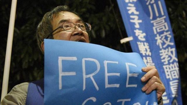 Một người biểu tình cầm tấm biển với dòng chữ