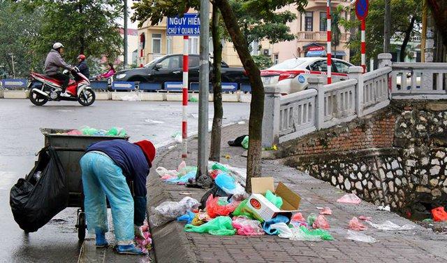 Những công nhân phải đi gom rác để cho vào xe rác sau khi người dân thả cá chép về trời