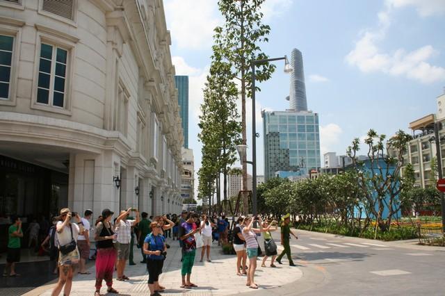 Còn những du khách này thì tranh thủ chụp trụ sở UBND TP.HCM, một chứng tích lịch sử, khi dạo chơi quảng trường mới trên đường Nguyễn Huệ.
