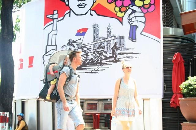 Đôi du khách quốc tế địu con chơi lễ khiến nhiều người nhìn theo mỉm cười vì hình ảnh khá dễ thương.