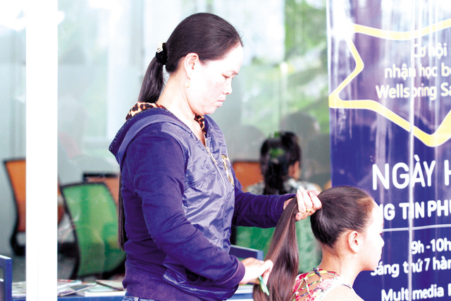 """Một phụ huynh tranh thủ buộc lại tóc cho con trước khi bước vào phần thi vòng sơ tuyển """"Giọng hát Việt nhí"""" tại Hà Nội.  Ảnh: Duy Anh"""