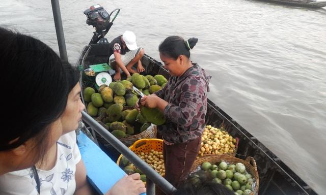 Chủ hàng không ngại bổ hoa quả ngay trên thuyền để khách mua ăn thử.