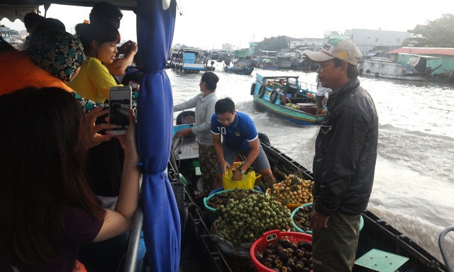 Không cần đợi chủ hàng tiếp thị, vị nam du khách nhảy hẳn sang thuyền hàng cẩn thận lựa từng quả thơm ngon để làm quà cho người thân.