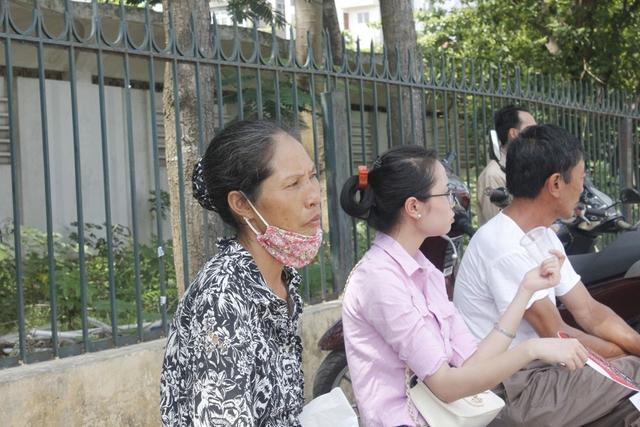 Cô Nguyễn Thị Mai (ngồi ngoài cùng bên trái) đang ngồi chờ con bên ngoài trường thi.Ảnh: Q.Huy