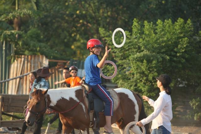 Bé Khôi Nguyên, 10 tuổi, với bài tập ngồi ngang giữ thăng bằng và tung hứng vòng.