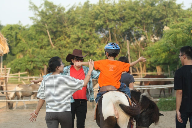 Bé Minh Tùng, 6 tuổi bị bại não, sau 10 buổi tập đã tự tin dang hai tay trên lưng ngựa.