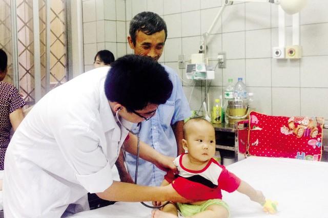 Cháu Đồng Quốc Việt được BS Phạm Văn Hưng khám trước khi xuất viện vào ngày 18/8.  Ảnh: Võ Thu