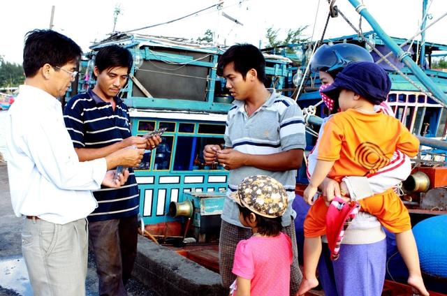 Cán bộ dân số huyện Cam Lâm - Khánh Hòa tư vấn các biện pháp tránh thai an toàn cho ngư dân miền biển.  Ảnh: Dương Ngọc