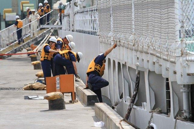 ...thủy thủ đoàn nhanh chóng làm công việc để tàu neo đậu an toàn...