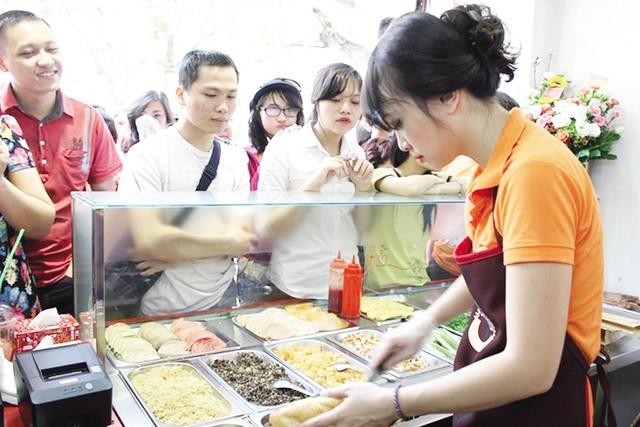 Minh Nhật tất bật trong ngày khai trương cửa hàng bánh mỳ. Ảnh: TL