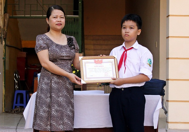 Hiệu trưởng trường THCS Tây Mỗ, cô Đỗ Thị Ánh Tuyết trao giấy khen cho em Hưng