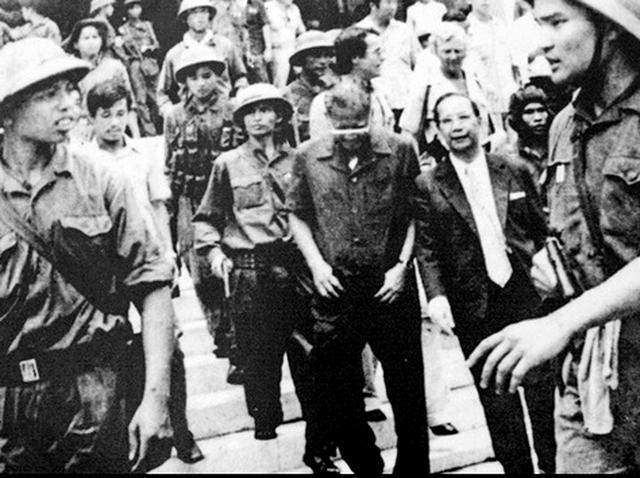 Đại úy Thệ (bìa phải) tay cầm súng ngắn, áp giải Dương Văn Minh ra Đài phát thanh để đọc lời tuyên bố đầu hàng. Ảnh: TL