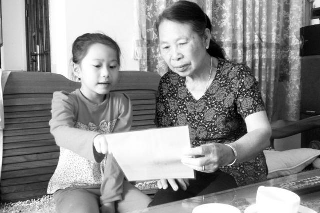 """Bà Lịch hào hứng kể lại chuyện """"Ba đảm đang"""" với cháu gái.Ảnh: Tịnh Tâm"""