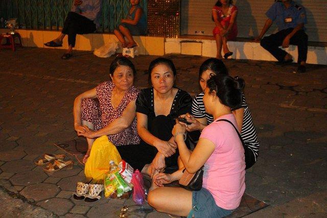 Một số người chuẩn bị đồ ăn sáng và kiên trì ngồi đợi bên vỉa hè.