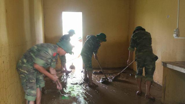 Dọn dẹp bùn đất tràn vào phồng y tế và phòng học của học sinh..