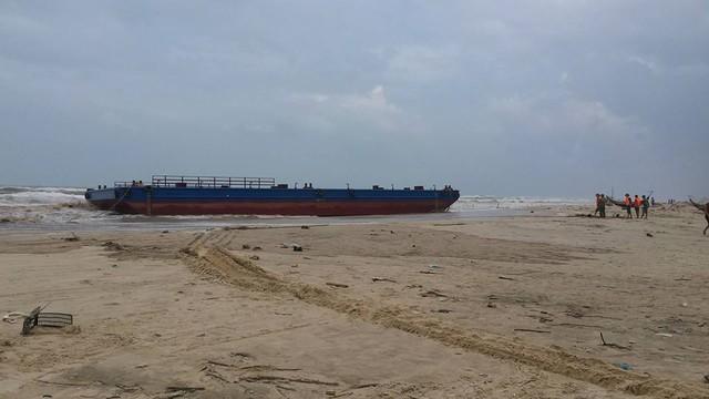 Xà lan gặp nạn bị các thuyền viên tàu ĐNa - 0494 chặt néo trôi dạt vào bờ. Ảnh: Lê Chung