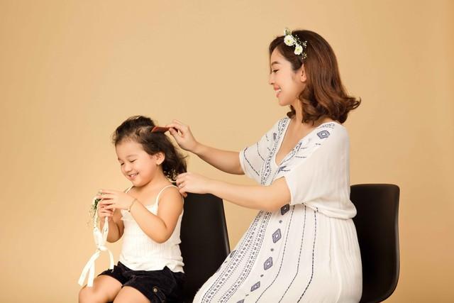 Bé Na rất thích được mẹ làm điệu nên đã vui vẻ ngồi yên để mẹ chải tóc và cài nơ.